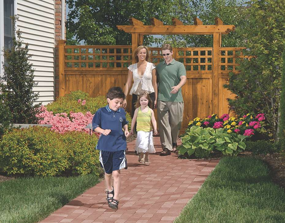 family walking on path in landscaped backyard