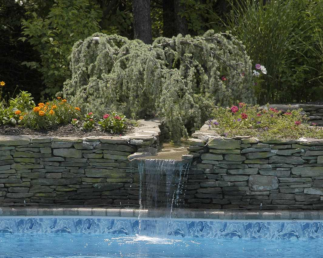 waterfall-into-pool-with-flowers-behind-it-1065x850